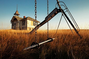 The long since closed school in Savoy, Montana falling into disaray on the Montana plains surrounded by tall grass and old playground equipment